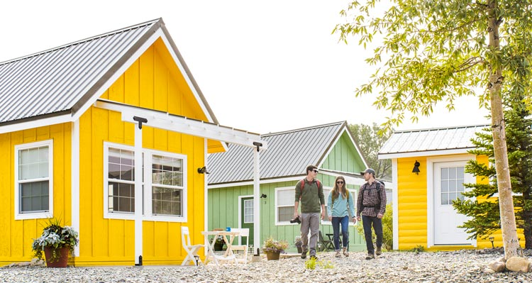 A group of three young adults ready for adventure walk among a group of colorful tiny homes