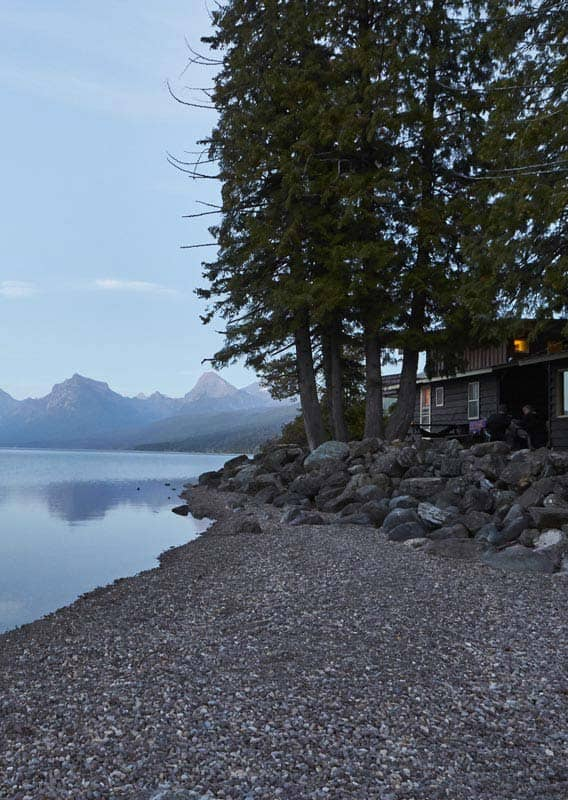 A rustic cabin sits at the shore of a serene lake, with mountains across.