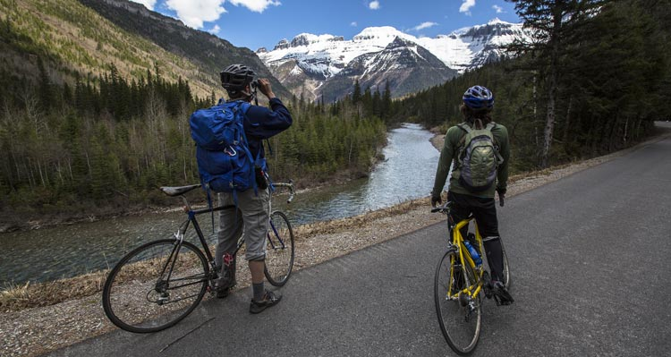 Two cyclists stop to enjoy and take photos of a view of a creek and snow-covered mountains.
