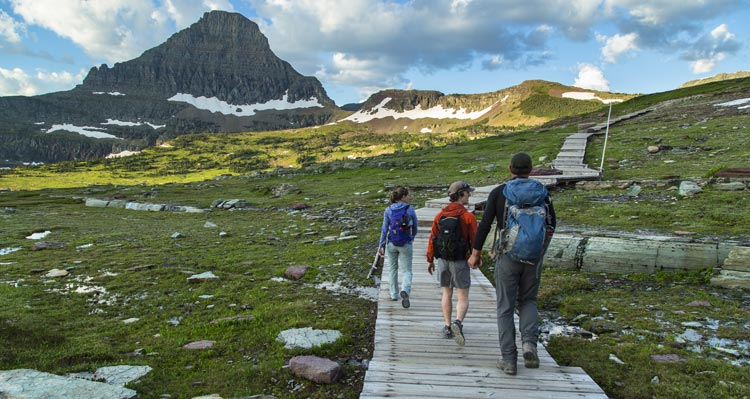 Three people walk along a boardwalk in an green, mountainous meadow