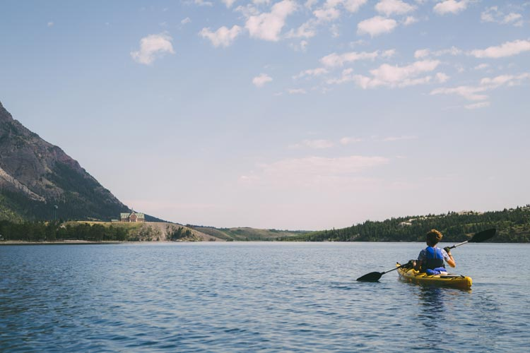 A kayaker paddles on a lake towards the Prince of Wales Hotel, at the meeting of grasslands and mountains