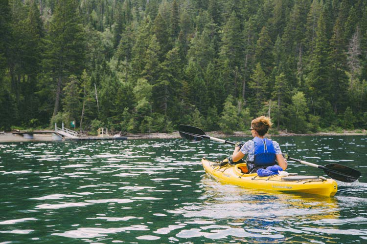 A kayaker paddles towards a dock on a forested lakeshore