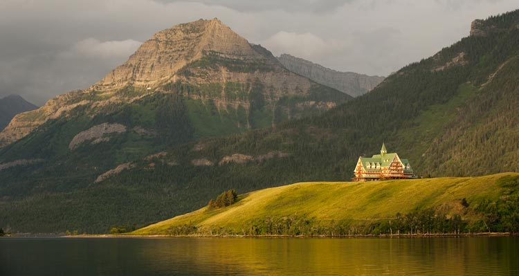 The Prince of Wales Hotel stands on a hill above a lake with mountains behind.