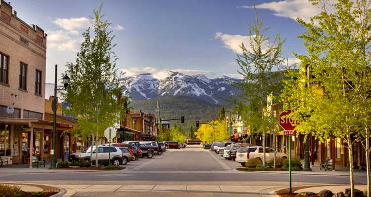 A view down Central Ave in Whitefish, MT. A tree-lined street with a view towards a snow-capped mountain.
