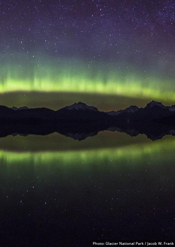 A night time view of mountains and green aurora across a lake.