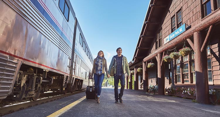 Two people walk between a train and the Amtrak train station.