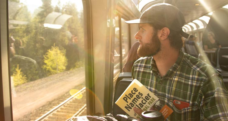 A man looks onto forests outside the window of a train.