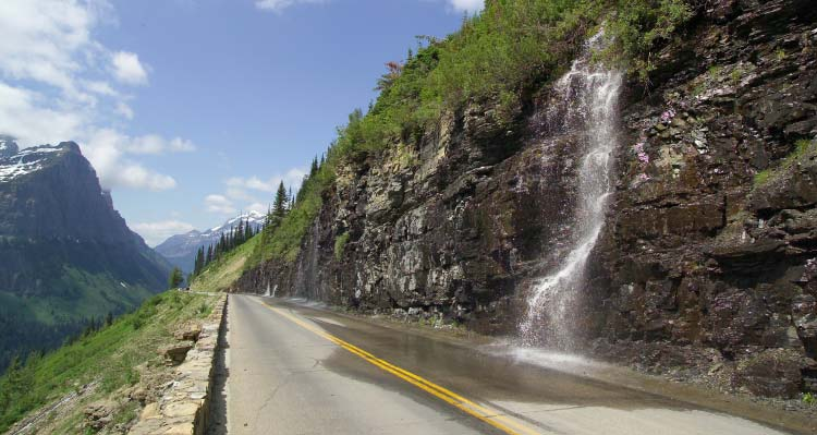 A waterfall splashes into a road running alongside a mountain.
