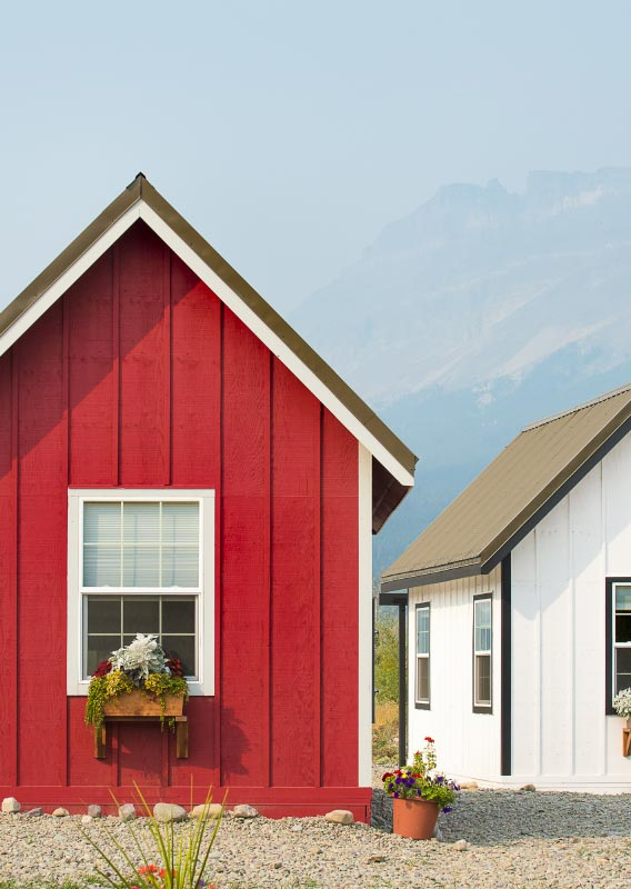 A red and white tiny home are surrounded by planters of flowers.