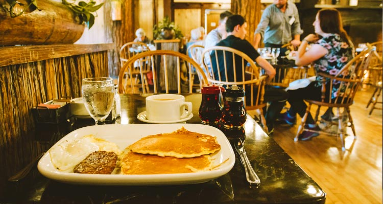 A breakfast plate of pancakes, eggs and sausage in a rustic dining room.