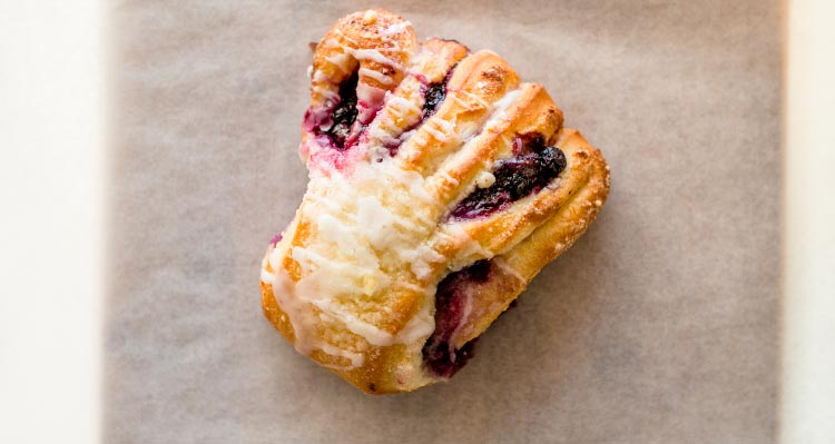 A pastry filled with purple jelly on parchment paper.
