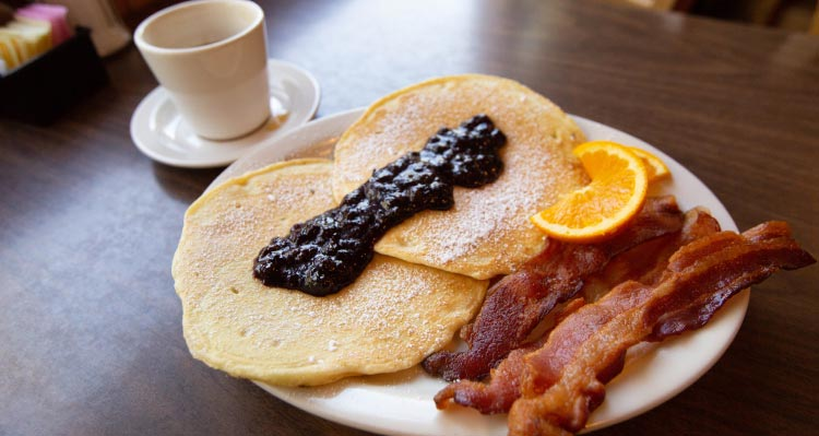 A breakfast of pancakes and jam with bacon an orange slice and coffee cup.
