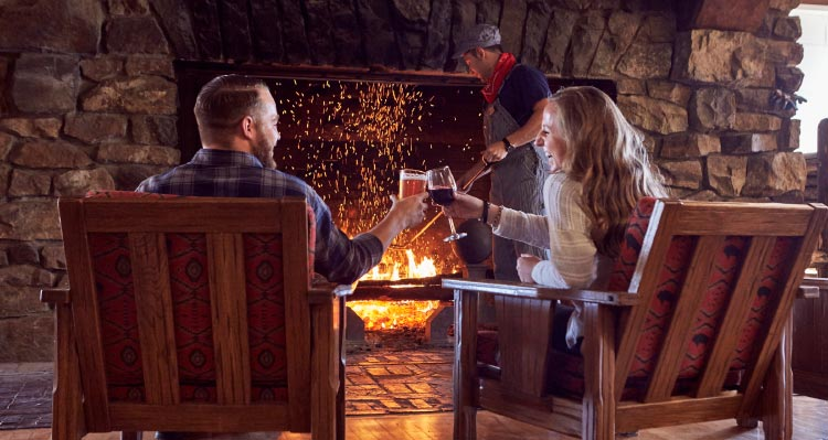 A couple cheers a drink next to a roaring fireplace.