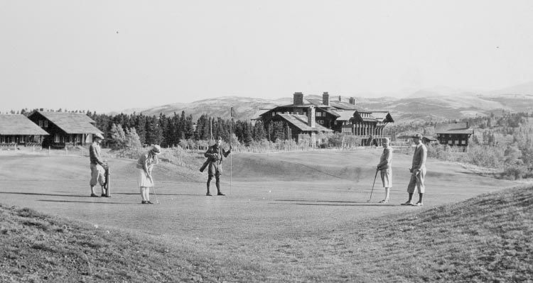 A group of people golf near a large lodge