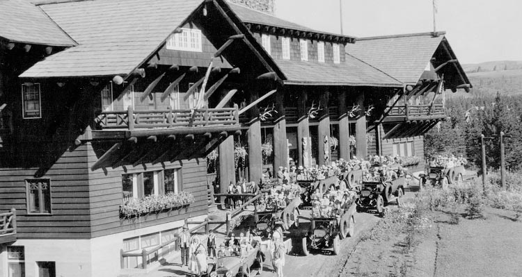 A historic image of cars outside a large wooden lodge.