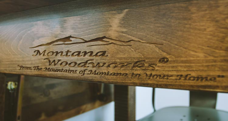 The underside of a table shows the Montana Woodworks logo engraved.