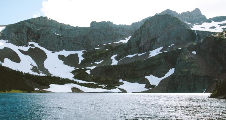 A view across a lake towards towering craggy mountains.