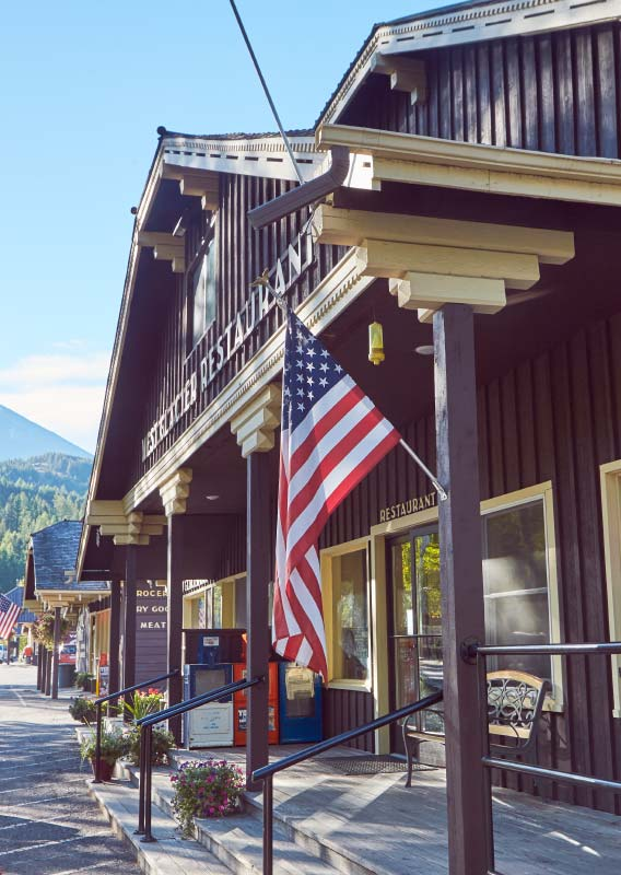 A wooden restaurant building with an American flag hanging from the entry post.