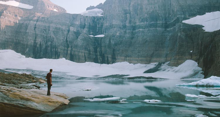 A hiker stands at the edge of a mountain lake surrounded by rocky cliffs and ice.