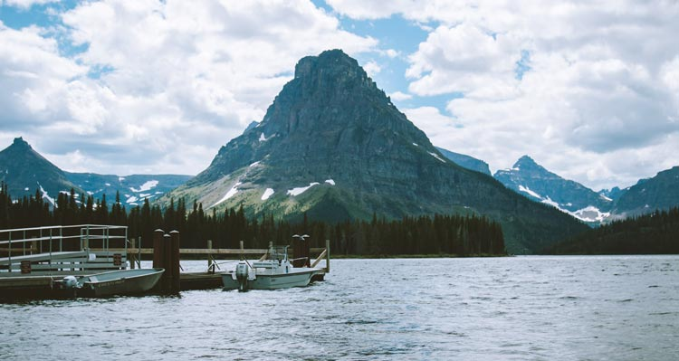 A prominent rocky mountain rises behind a crisp lake.