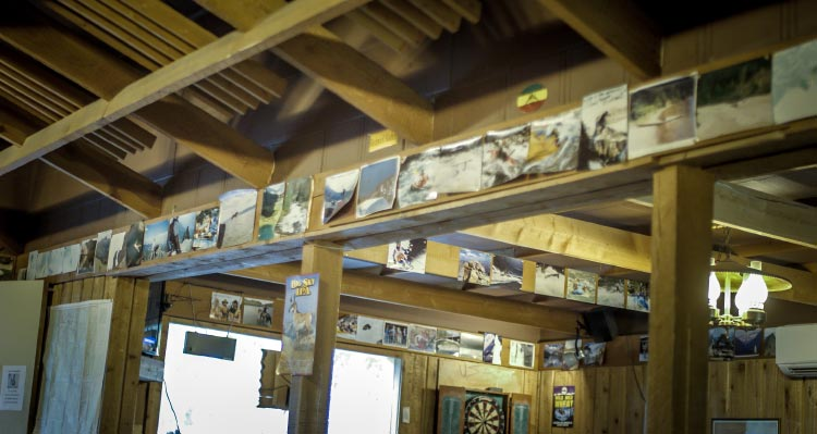 The wall inside a wooden bar is covered with historic photos of adventure.
