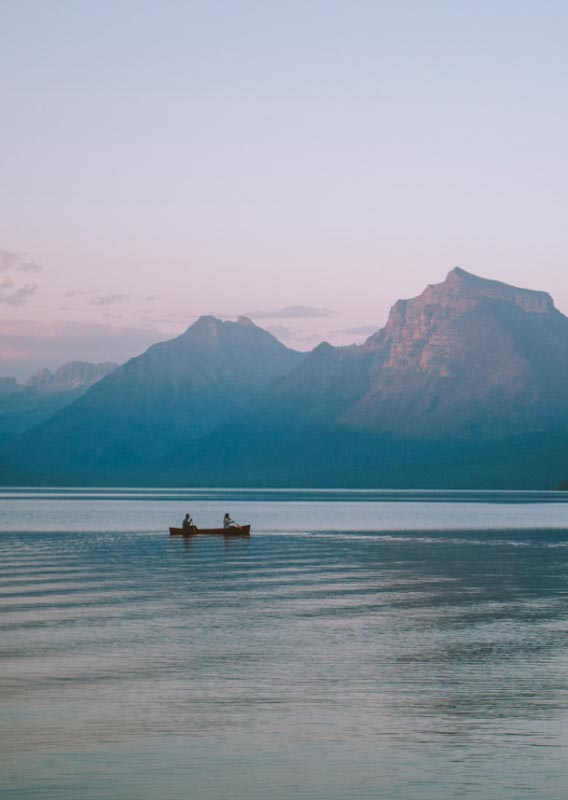 Two canoers paddle on a clear lake with mountains glowing in a sunset.