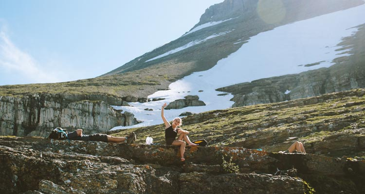 A hiker waves from a rocky ledge in front of a snow-covered mountainside.