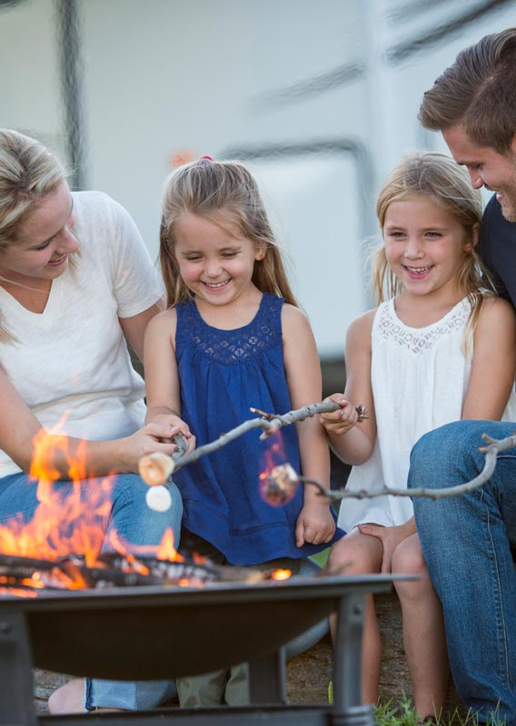 A family roasts marshmallows over a firepit.