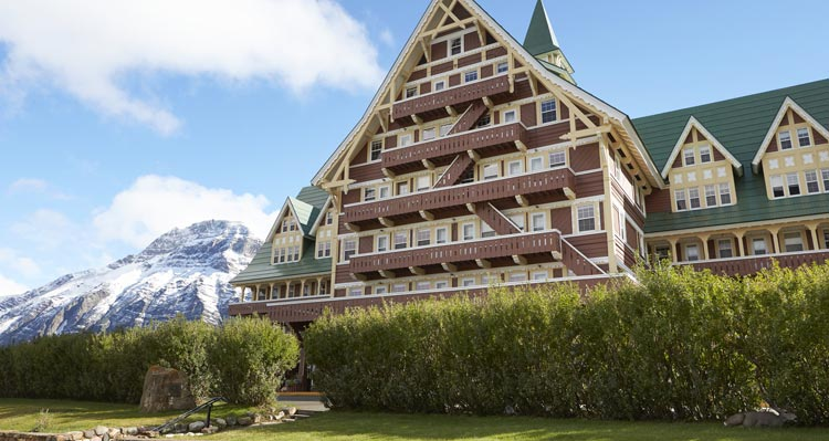 The Prince of Wales Hotel, with a gabled green roof with snow covered mountains behind.