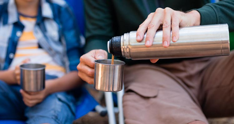 A cup of coffee poured from a thermos.