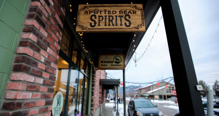 A hanging wooden sign for Spotted Bear Spirits above the sidewalk in downtown Whitefish.