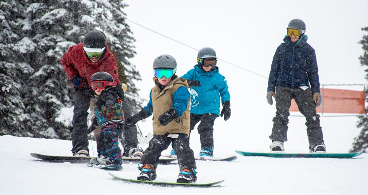 Three kids get ready to snowboard with their parents.