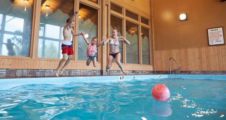 3 kids jump into an indoor swimming pool