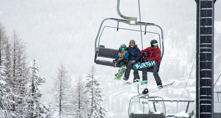 A family rides a ski lift on a snowy day.