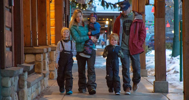 A family of five walk alongside shops under an awning in downtown Whitefish.