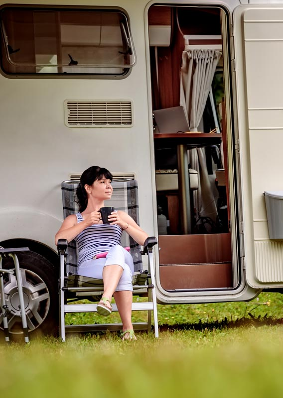 A woman sits outside an RV with a cup of coffee.