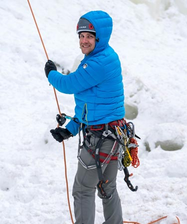 An ice climbing guide in a blue jacket holds on to a rope.