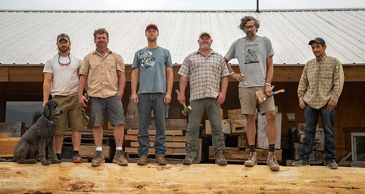A team of wordworkers stand atop a large timber.