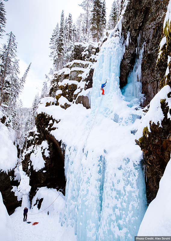 An Ice climber on the side of a frozen waterfall attached by rope to a belayer below.