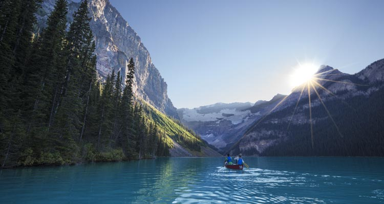 A pair of canoers paddle on a blue lake surrounded by forest-covered mountains.