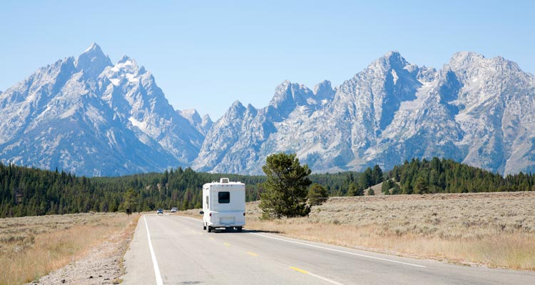An RV drives on an open road towards jagged mountain peaks.