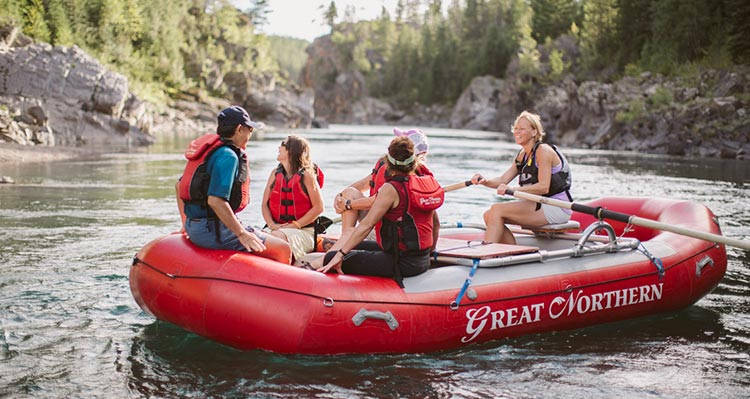 Five people sit and paddle a red raft.