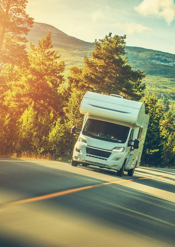 An RV drives down a sunny road below forested hillsides.