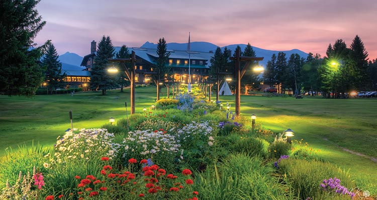 Flowerbed gardens stretch across a green lawn towards a large wooden lodge.