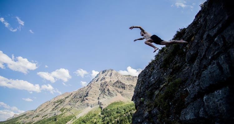 A man jumps from a cliffside into a lake.