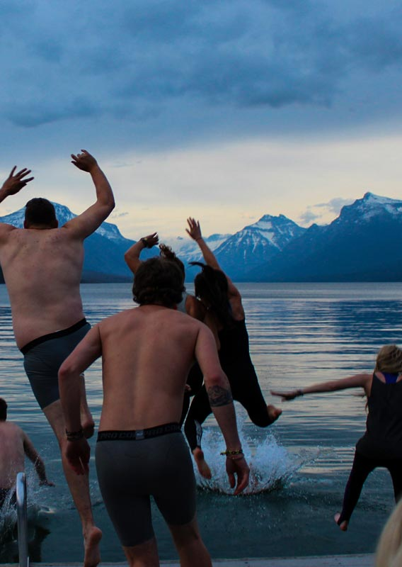 A group of people jump into a lake surrounded by mountains