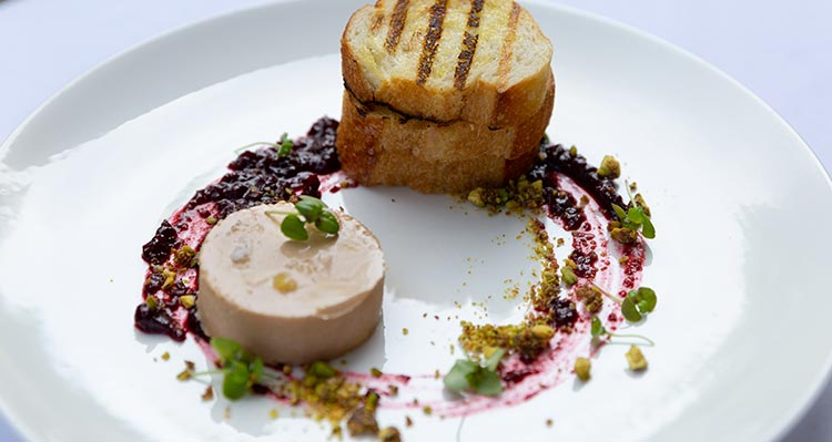 A finished plate of pate, toasted bread with jam garnish