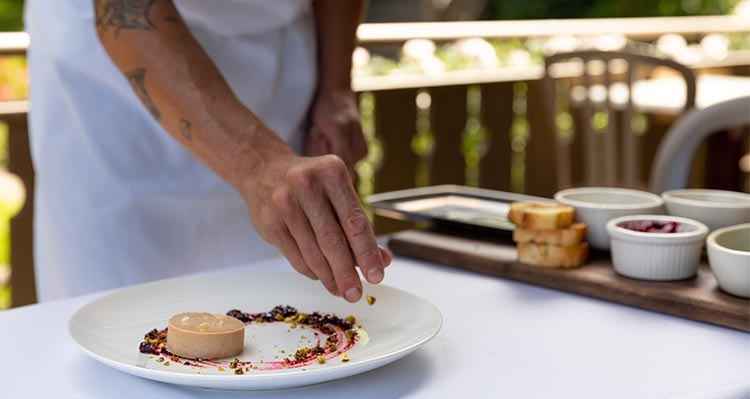 A chef puts the finishing touches on a plate of pate.