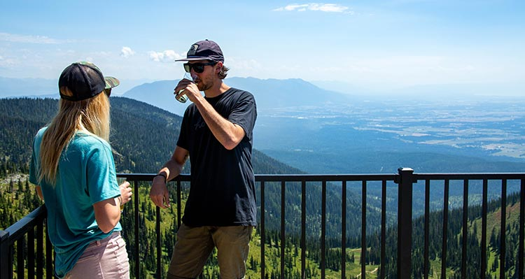Two people stand on a mountaintop balcony.