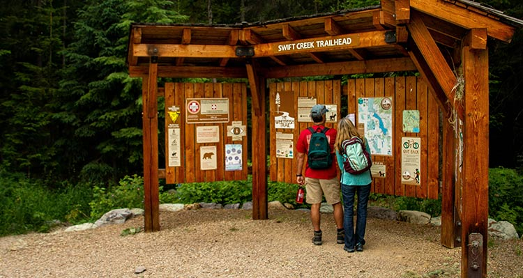 Two people look at a trailhead information board.